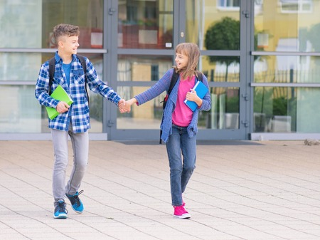 Happy children - boy and girl with books and backpacks on the first or last school day. Schoolchildren celebrating end of term. Students to complete academic year. Full length outdoor portrait.