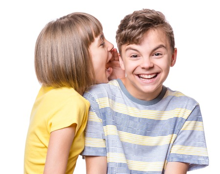 Foto de Friendship - beautiful girl whispering something to teen boy. Portrait of happy brother and sister, isolated on white background. Funny couple children - first love. - Imagen libre de derechos