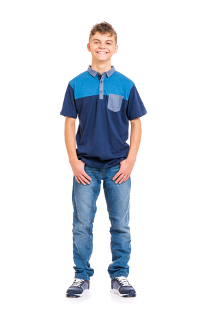 Foto de Full length portrait of young caucasian teen boy, isolated on white background. Funny teenager looking at camera and smiling. Handsome child with hands in pockets. - Imagen libre de derechos