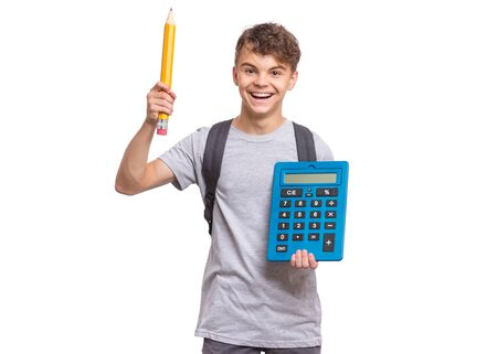 Foto de Smart student holding big calculator and pencil. Portrait of funny cute teen boy looking at camera, isolated on white background. Happy smiling child Back to school. - Imagen libre de derechos