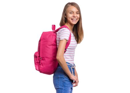 Foto de Student teen girl with backpack looking at camera. Portrait of cute smiling schoolgirl with hands in pockets, isolated on white background. Happy child Back to school. - Imagen libre de derechos