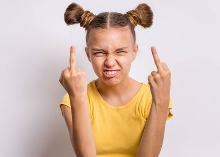 Photo for Portrait of angry teen girl showing middle finger, on gray background. Beautiful caucasian young teenager making grimace and obscene gesture. Cute child shows bad sign and looking at camera. - Royalty Free Image