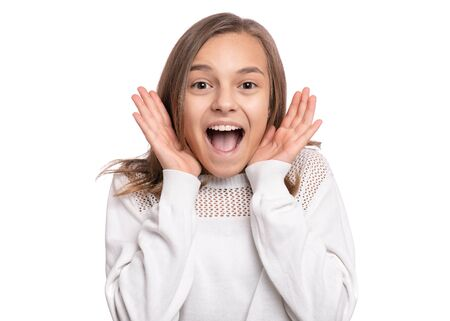 Photo pour Surprised happy young teen girl, isolated on white background. Funny child looking at camera with mouth open in amazement. Emotional portrait of caucasian teenager. - image libre de droit