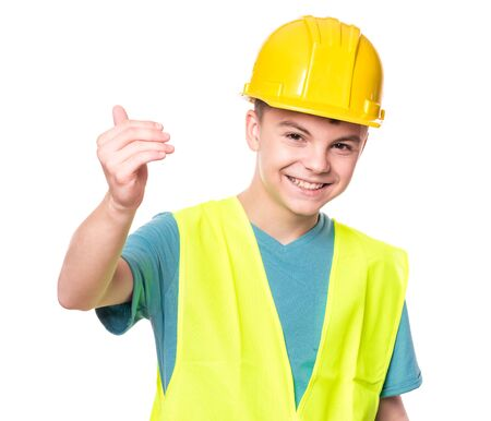 Photo pour Funny Handsome Teen Boy wearing Safety Jacket and yellow Hard Hat. Portrait of Happy Child Makes Hand Gesture and Looking at Camera, isolated on white background. - image libre de droit