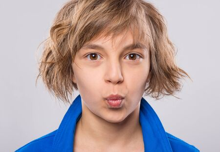 Photo for Beautiful Caucasian Teen Girl on gray background. Schoolgirl sending blowing Kiss with pout Lips looking at camera. Happy Child - emotional Portrait close-up. - Royalty Free Image