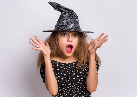 Photo pour Happy halloween concept. Surprised Teen girl in witch black hat looking at camera in amazement on grey background. Cute child in witch halloween costume shouting, opening eyes and mouth with shock. - image libre de droit