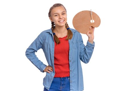 Foto de Portrait of beautiful young teen girl holding wooden palette and paint brush, isolated on white background. Smiling child with art palette and artist brush in hands. Items for children creativity. - Imagen libre de derechos