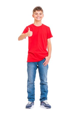 Foto de Full length portrait of young caucasian teen boy isolated on white background. Funny teenager making thumb up gesture. Handsome child looking at camera and smiling. - Imagen libre de derechos