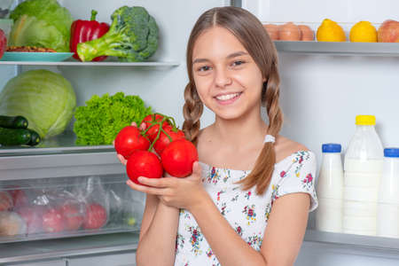 Photo for Smiling beautiful young teen girl holding fresh red tomatoes while standing near open fridge in kitchen at home. Portrait of pretty child choosing food in refrigerator full of healthy products - Royalty Free Image