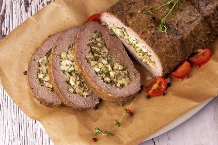 Photo pour Meatloaf stuffed with eggs and fried onions. A large portion of meat is cut and served in a rustic style.  Close up and horizontal orientation. Top view.  - image libre de droit