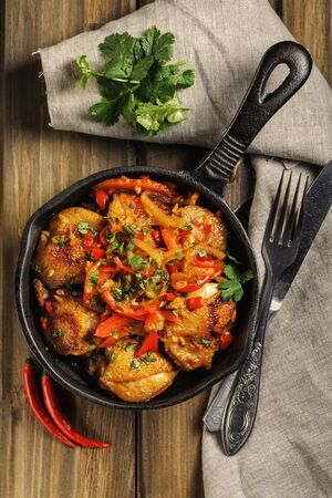 Photo for Fried chicken in spicy sauce with vegetables. Cooked in a cast iron pan. The pan is on a dark wooden background. Next is a natural linen napkin. Top view. Vertical.  - Royalty Free Image