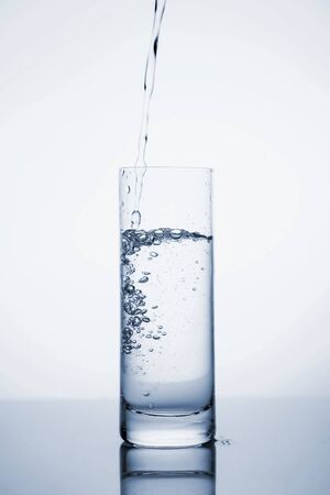 Photo pour Clear mineral water is poured into a glass with ice. Fluid in motion. Copy space. Close up and vertical orientation. - image libre de droit