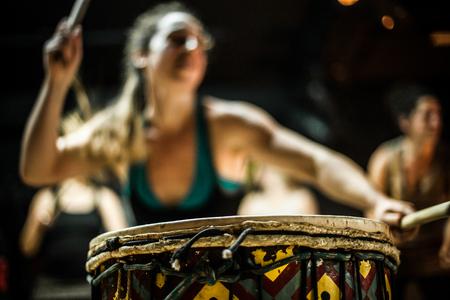 Blurry girl dancing and playing doun doun with two drum sticks