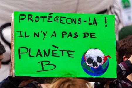French sign at ecological demonstration. A French banner held by an environmentalist during a protest against climate change is seen close-up. The sign says protect it, there is no planet b.