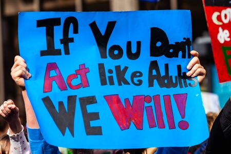 Foto de A colorful poster is seen close-up, held in the hands of an environmentalist, saying if you don't act like adults, we will, during a street demonstration - Imagen libre de derechos