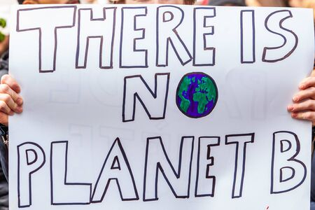 Photo pour A home made placard is viewed close up, reading there is no planet b, as environmentalists stage a city demonstration against global warming - image libre de droit