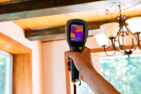 Photo pour Indoor damp & air quality (IAQ) testing. A handheld IR thermovision camera is seen closeup, checking the insulation levels inside a domestic home with blurred timber beams in background. - image libre de droit