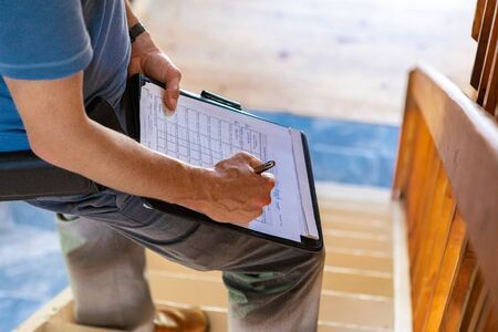 Photo for Indoor damp & air quality (IAQ) testing. A close up and high angle view of a professional male wearing blue t-shirt, writing out forms during a home inspection, standing on stairs with copy-space. - Royalty Free Image