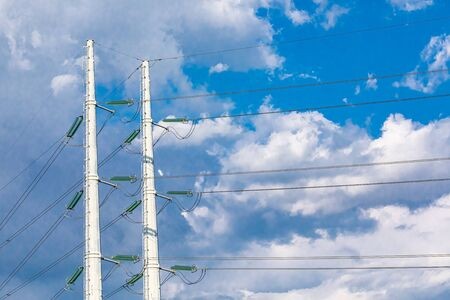 Photo pour Two utility poles are viewed from below, supporting overhead electric cables, medium voltage cables fixed to tall white pylons against a cloudy skyscape. - image libre de droit