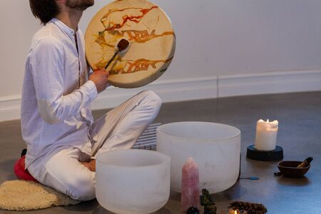 Foto de Man dressed in white, sitting on a sheep skin and playing with sacred drum with various objects displayed like stones, candles and more - Imagen libre de derechos