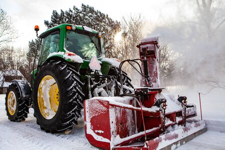 Photo for Red snowblower blowing snow installed on a green tractor clearing the streets after a winter storm, through the sun - Royalty Free Image