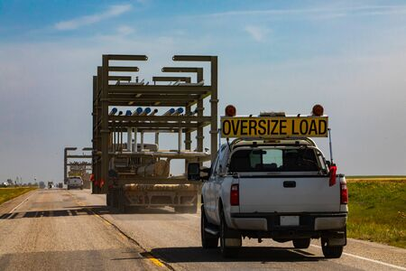 Photo for Oversize loaded truck traveling along road at a sunny day. Pickup following behind for security. Coutryside grasslands and plains in the background. - Royalty Free Image