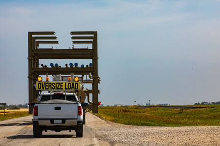 Photo for Oversize loaded truck traveling along road at a sunny day. Pickup following behind for security. Coutryside grasslands at background. - Royalty Free Image