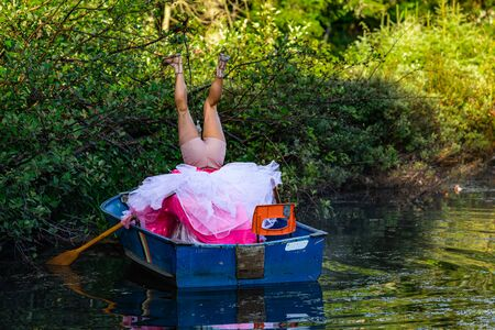 Foto de Behind view of a person in a small wooden boat on water making strange upside down positions in a funny dress - Imagen libre de derechos