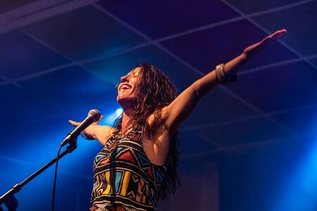Foto de a female musician is viewed from a low angle as she sings and smiling with the audience with her hands raised up during a performance - Imagen libre de derechos