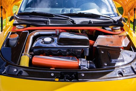 Foto de Yellow small Car under hood showing high performance engine tuning and modification, red, silver, chrome and carbon fiber clean parts - Imagen libre de derechos