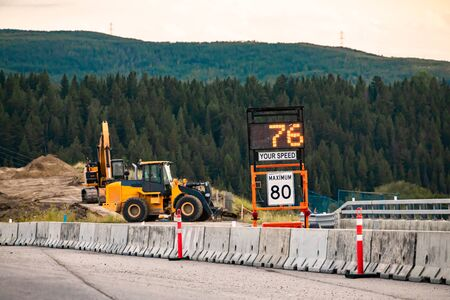 Photo for Radar Speed Sign displays vehicle speed on variable sign, your speed is 76, 80km maximum limitation, road work zone Machines Excavators on background - Royalty Free Image