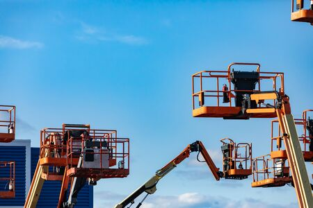 Photo pour A group of raised cherry pickers, aerial work platforms, are seen in an elevated state in storage, hydraulic mobile cranes with copy space - image libre de droit