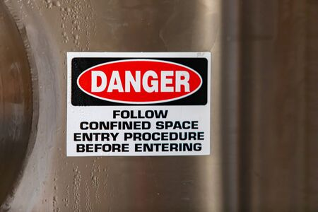 Photo pour DANGER, FOLLOW CONFINED ENTRY PROCEDURE BEFORE ENTERING, warning vinyl sticker sign on stainless steel cold industrial tank, with copy space - image libre de droit