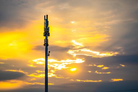 Photo for A wide angle view of a monopole cell site tower at sunset. Golden backlit silhouetted cellular base station with scattered clouds and copy space - Royalty Free Image