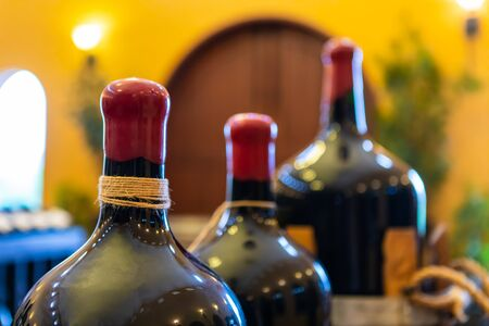 Foto de set of red wax-sealed wine glass big size magnum bottles top selective focus close up, wines winery tasting room interior decor background - Imagen libre de derechos