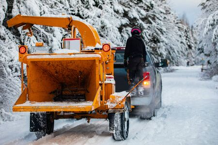 A tree surgeon is seen trying to earn a living outdoors during winter, towing heavy equipment through thick snow on a street in rural Quebec, Canada