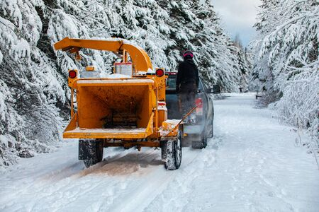 A wide view of an arborist standing on the back of a truck pulling a mobile tree chipper on a rural road during winter, heavy snow causes disruption