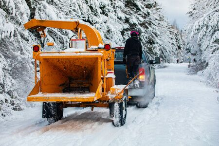 A wide view of an arboriculturist, tree surgeon or landscape gardener, towing a mobile wood chipper with a pickup truck down a snow covered street