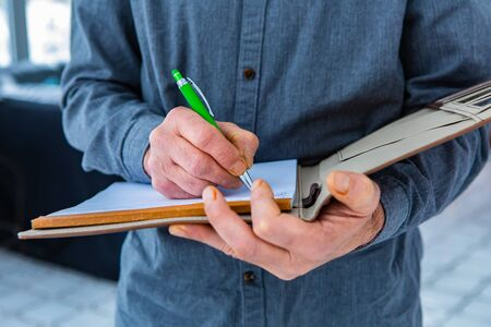 Photo for A close up and selective focus shot of a notebook with a leather cover held by inspectors hands with a green pen. as he taking and writes notes - Royalty Free Image