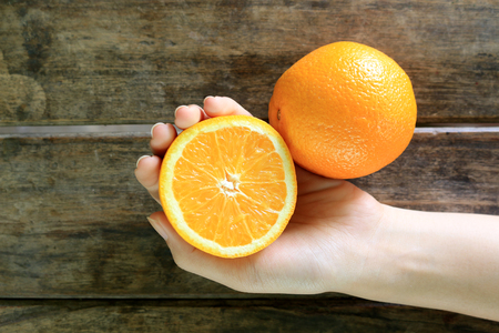 Hand Holding Orange fruit on wooden table background