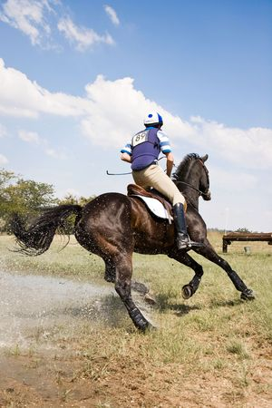 Horse and rider turning for the next fence, after successfully negotiating a water jump, in a cross country event.