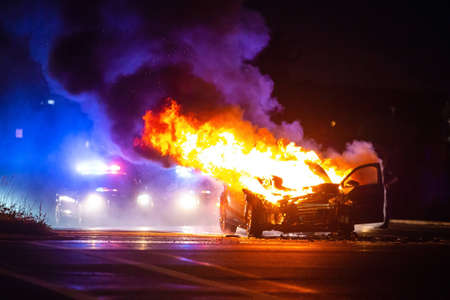 Photo for Car on fire at night with police lights in background - Royalty Free Image