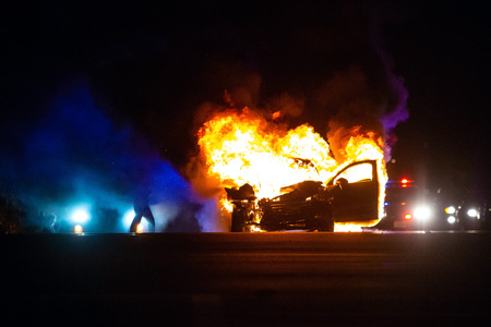 Photo pour Car on fire at night with police lights in background - image libre de droit