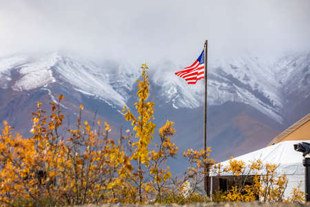 USA flag proudly raised at Denali National park station in Alaska at day