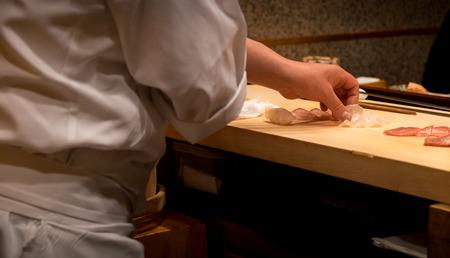 Foto de Japanese chef slicing fresh raw fish for sushi - Imagen libre de derechos