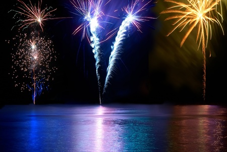 Foto de Blue, red, white and yellow colorful fireworks above the river. Holiday celebration. - Imagen libre de derechos