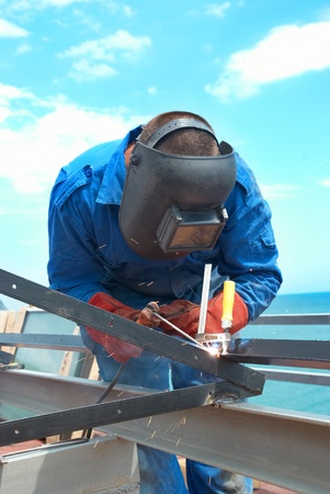 Welder at the factory working with metal construction