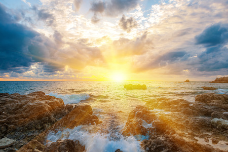 Photo pour Sunset on the beach with waves, sea, rocks and dramatic sky. Landscape with sun in the centre - image libre de droit