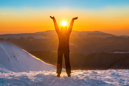 Woman on the top of winter mountain holding sun in her hands