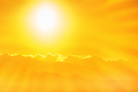 Beautiful orange sunset in the sky. Big shining sun with sunrays